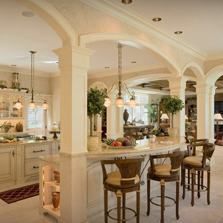 Design ideas for a large victorian l-shaped open plan kitchen in Houston with a drop-in sink, raised-panel cabinets, white cabinets, quartz benchtops, white splashback, subway tile splashback, stainless steel appliances, porcelain floors and multiple islands.