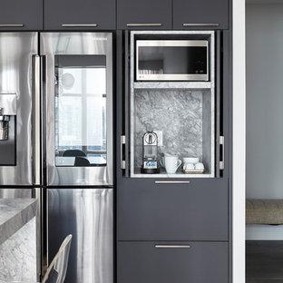 Idées déco pour une cuisine ouverte moderne en L de taille moyenne avec un évier encastré, un placard à porte plane, des portes de placard grises, un plan de travail en quartz, une crédence grise, une crédence en dalle de pierre, un électroménager noir, un sol en bois brun, un îlot central, un sol beige et un plan de travail gris.