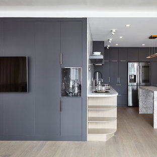 Mid-sized minimalist l-shaped medium tone wood floor and beige floor open concept kitchen photo in Toronto with an undermount sink, flat-panel cabinets, gray cabinets, quartzite countertops, gray backsplash, stone slab backsplash, black appliances, an island and gray countertops