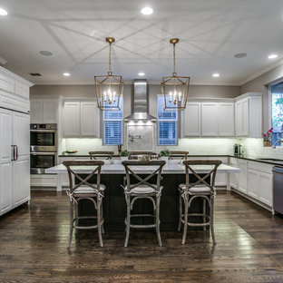 Photo of a large transitional u-shaped kitchen in Dallas with shaker cabinets, white cabinets, quartz benchtops, white splashback, limestone splashback, stainless steel appliances, medium hardwood floors, with island, brown floor, black benchtop and an undermount sink.