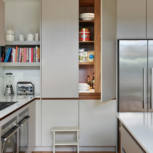 Photo of a large contemporary l-shaped kitchen/diner in London with flat-panel cabinets, beige cabinets, composite countertops, medium hardwood flooring, an island, beige floors and white worktops.