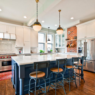 Large traditional open concept kitchen ideas - Large elegant l-shaped medium tone wood floor open concept kitchen photo in Nashville with a double-bowl sink, recessed-panel cabinets, white cabinets, marble countertops, white backsplash, subway tile backsplash, stainless steel appliances and an island