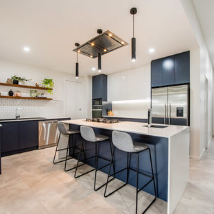 Contemporary kitchen in Brisbane with a drop-in sink, flat-panel cabinets, blue cabinets, white splashback, stainless steel appliances, with island, grey floor and white benchtop.