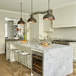 Inspiration for a classic galley kitchen in London with a submerged sink, shaker cabinets, white cabinets, white splashback, metro tiled splashback, stainless steel appliances, medium hardwood flooring, an island, brown floors and grey worktops.