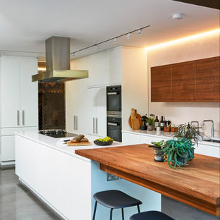 Photo of a contemporary l-shaped kitchen in London with a submerged sink, flat-panel cabinets, white cabinets, stainless steel appliances, concrete flooring, an island, grey floors and white worktops.
