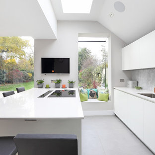 Photo of a contemporary kitchen in London with a double-bowl sink, flat-panel cabinets, white cabinets, grey splashback, a breakfast bar, grey floors and white worktops.