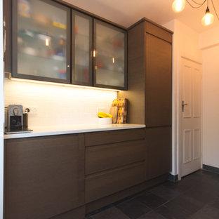 Idee per una piccola cucina ad U minimal chiusa con lavello integrato, ante di vetro, ante marroni, top in quarzite, paraspruzzi bianco, paraspruzzi con piastrelle in ceramica, elettrodomestici in acciaio inossidabile, pavimento in ardesia e nessuna isola
