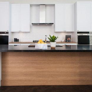 Bild på ett mellanstort nordiskt kök, med en dubbel diskho, skåp i shakerstil, vita skåp, bänkskiva i koppar, vitt stänkskydd, stänkskydd i tunnelbanekakel, rostfria vitvaror, betonggolv, en köksö och svart golv