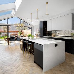 Mittelgroße Moderne Wohnküche mit Waschbecken, flächenbündigen Schrankfronten, schwarzen Schränken, Küchenrückwand in Metallic, Rückwand aus Metallfliesen, hellem Holzboden, Kücheninsel, beigem Boden und weißer Arbeitsplatte in London
