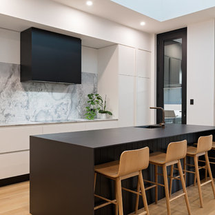 Photo of a contemporary galley kitchen in Adelaide with an integrated sink, flat-panel cabinets, white cabinets, grey splashback, black appliances, light hardwood floors, with island and black benchtop.
