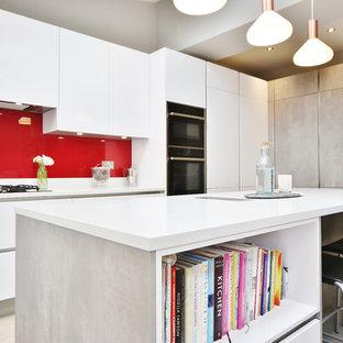 Foto di una cucina contemporanea di medie dimensioni con lavello sottopiano, ante lisce, ante turchesi, top in quarzite, paraspruzzi rosso, paraspruzzi con lastra di vetro, parquet chiaro, isola, pavimento marrone e top bianco
