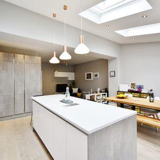 Idee per una cucina contemporanea di medie dimensioni con lavello sottopiano, ante lisce, ante turchesi, top in quarzite, paraspruzzi rosso, paraspruzzi con lastra di vetro, parquet chiaro, isola, pavimento marrone e top bianco