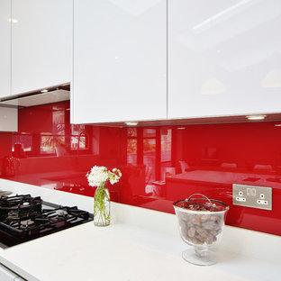 Immagine di una cucina contemporanea di medie dimensioni con lavello sottopiano, ante lisce, ante turchesi, top in quarzite, paraspruzzi rosso, paraspruzzi con lastra di vetro, parquet chiaro, isola, pavimento marrone e top bianco