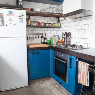 Imagen de cocina moderna con armarios con paneles lisos, puertas de armario azules, salpicadero blanco, salpicadero de azulejos tipo metro y electrodomésticos blancos