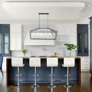 Design ideas for a large transitional l-shaped open plan kitchen in Toronto with recessed-panel cabinets, blue cabinets, wood benchtops, white splashback, dark hardwood floors, with island, brown floor, a drop-in sink, marble splashback and stainless steel appliances.