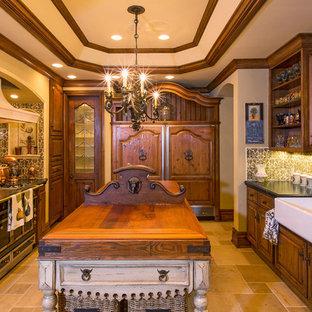 Immagine di una cucina vittoriana con lavello stile country, ante con bugna sagomata, ante in legno bruno, paraspruzzi multicolore, elettrodomestici da incasso e isola