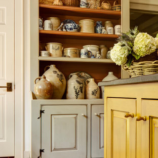 Design ideas for a small rustic u-shaped enclosed kitchen in Atlanta with a belfast sink, beaded cabinets, distressed cabinets, soapstone worktops, black splashback, stone slab splashback, stainless steel appliances, brick flooring and an island.