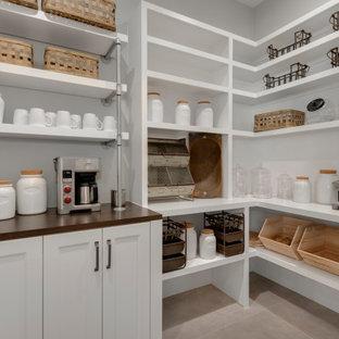 Landhaus Küche mit Vorratsschrank, Landhausspüle, Granit-Arbeitsplatte, Küchenrückwand in Weiß, Porzellan-Bodenfliesen, zwei Kücheninseln, grauer Arbeitsplatte und freigelegten Dachbalken in Austin