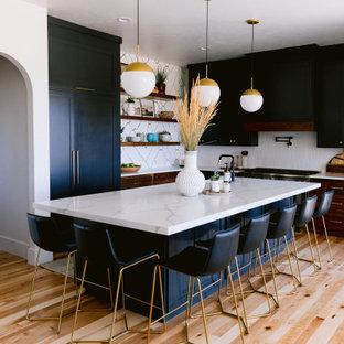 Ejemplo de cocina en L, rústica, abierta, con armarios estilo shaker, puertas de armario de madera en tonos medios, encimera de cuarzo compacto, salpicadero de azulejos de cerámica, una isla y encimeras blancas
