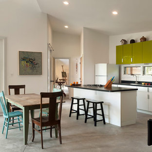 Inspiration for a small contemporary galley concrete floor eat-in kitchen remodel in DC Metro with a drop-in sink, flat-panel cabinets, green cabinets, white appliances, laminate countertops, white backsplash and an island