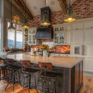 Inspiration for a large rural l-shaped kitchen/diner in Denver with a belfast sink, black cabinets, granite worktops, black splashback, integrated appliances, an island, brown floors, black worktops, medium hardwood flooring and beaded cabinets.