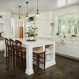 グランドラピッズのコンテンポラリースタイルのおしゃれなキッチン (エプロンフロントシンク、白いキャビネット、濃色無垢フローリング、茶色い床、クオーツストーンカウンター、黄色いキッチンパネル) の写真