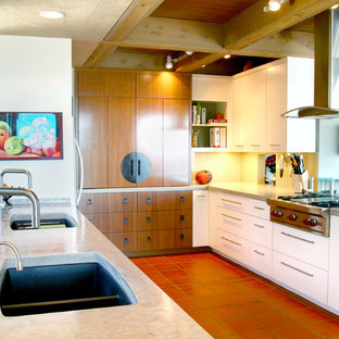This is an example of a mid-sized contemporary u-shaped open plan kitchen in Austin with an undermount sink, flat-panel cabinets, white cabinets, concrete benchtops, green splashback, glass sheet splashback, stainless steel appliances, terra-cotta floors, a peninsula and pink floor.