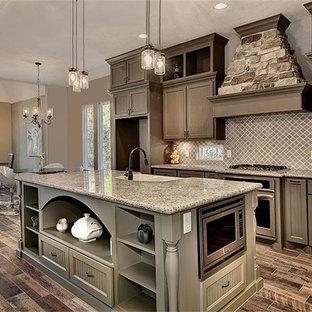 Foto på ett mellanstort vintage blå kök, med en rustik diskho, skåp i shakerstil, bruna skåp, granitbänkskiva, beige stänkskydd, stänkskydd i keramik, rostfria vitvaror, klinkergolv i porslin, en köksö och brunt golv