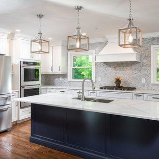Inredning av ett klassiskt stort vit vitt kök, med en dubbel diskho, skåp i shakerstil, vita skåp, bänkskiva i kvarts, grått stänkskydd, stänkskydd i mosaik, rostfria vitvaror, mellanmörkt trägolv, en köksö och brunt golv