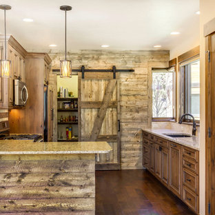 Inredning av ett rustikt avskilt, litet u-kök, med en undermonterad diskho, luckor med infälld panel, skåp i mellenmörkt trä, bänkskiva i terrazo, beige stänkskydd, stänkskydd i stenkakel, rostfria vitvaror, mellanmörkt trägolv och en halv köksö