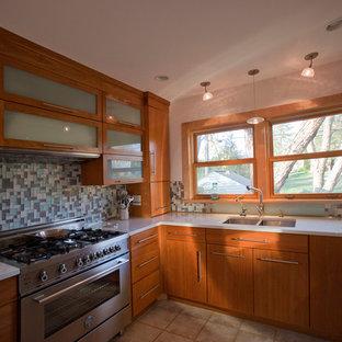 シーダーラピッズの広いコンテンポラリースタイルのおしゃれなキッチン (ダブルシンク、フラットパネル扉のキャビネット、中間色木目調キャビネット、マルチカラーのキッチンパネル、ガラスタイルのキッチンパネル、シルバーの調理設備、人工大理石カウンター、セラミックタイルの床、アイランドなし、ベージュの床) の写真