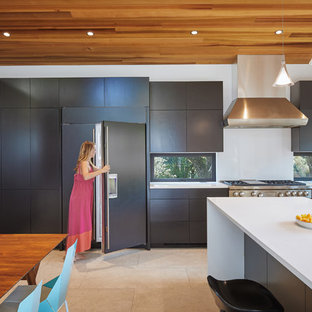 Inspiration for a midcentury eat-in kitchen in Austin with a drop-in sink, black cabinets, quartz benchtops, stainless steel appliances, ceramic floors, with island, grey floor and white benchtop.