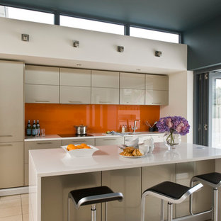 This is an example of a mid-sized contemporary single-wall kitchen in Other with beige cabinets, orange splashback and with island.