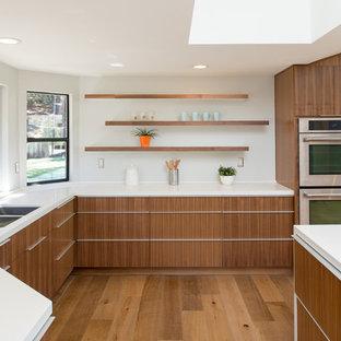 Diseño de cocina en U, minimalista, grande, abierta, con fregadero bajoencimera, armarios con paneles lisos, puertas de armario de madera en tonos medios, encimera de cuarzo compacto, salpicadero blanco, electrodomésticos de acero inoxidable, suelo de madera en tonos medios y una isla