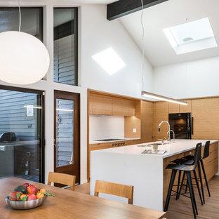 Idéer för att renovera ett mellanstort 50 tals vit vitt kök och matrum, med släta luckor, skåp i ljust trä, bänkskiva i kvarts, vitt stänkskydd, ljust trägolv, en köksö, en undermonterad diskho och svarta vitvaror