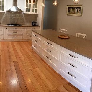 メルボルンの大きいモダンスタイルのおしゃれなキッチン (ドロップインシンク、黄色いキャビネット、クオーツストーンカウンター、グレーのキッチンパネル、サブウェイタイルのキッチンパネル、白い調理設備、淡色無垢フローリング) の写真
