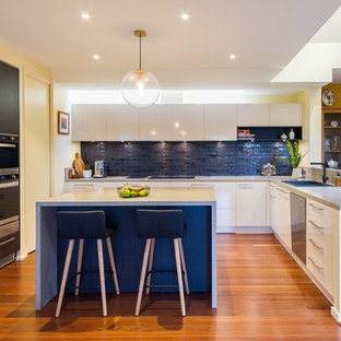 Large contemporary u-shaped open plan kitchen in Melbourne with flat-panel cabinets, quartz benchtops, black splashback, subway tile splashback, medium hardwood floors, with island, grey benchtop, a drop-in sink, black cabinets, black appliances and brown floor.