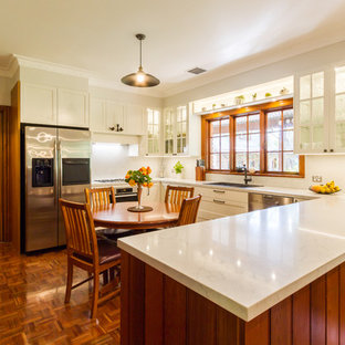 Design ideas for a mid-sized traditional u-shaped eat-in kitchen in Melbourne with a drop-in sink, shaker cabinets, white cabinets, marble benchtops, white splashback, marble splashback, stainless steel appliances, medium hardwood floors, a peninsula, brown floor and white benchtop.
