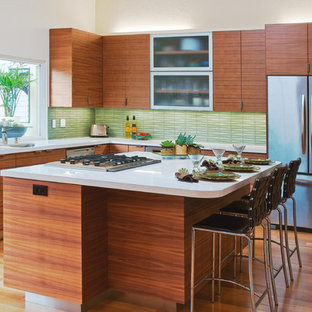This is an example of a midcentury l-shaped eat-in kitchen in San Francisco with stainless steel appliances, flat-panel cabinets, medium wood cabinets, green splashback, an undermount sink, solid surface benchtops, light hardwood floors, with island and glass tile splashback.