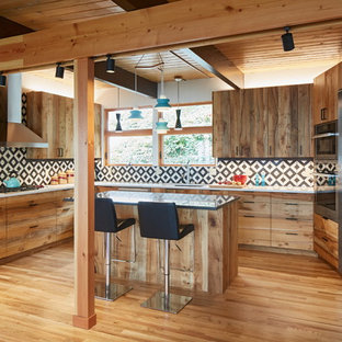 Photo of a mid-sized country u-shaped kitchen in Portland with an undermount sink, flat-panel cabinets, medium wood cabinets, quartz benchtops, multi-coloured splashback, cement tile splashback, stainless steel appliances, medium hardwood floors, with island and beige floor.