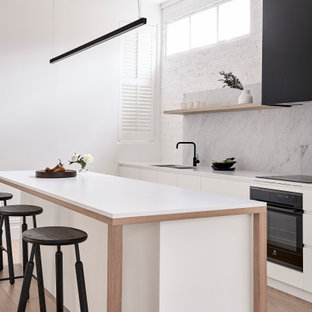 Inspiration for a contemporary galley kitchen in Melbourne with an undermount sink, flat-panel cabinets, white cabinets, grey splashback, stone slab splashback, black appliances, light hardwood floors, with island, beige floor and white benchtop.
