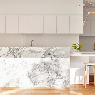 Inspiration for a contemporary l-shaped kitchen in Geelong with white cabinets, marble benchtops, with island, flat-panel cabinets, stainless steel appliances, medium hardwood floors, brown floor and white benchtop.