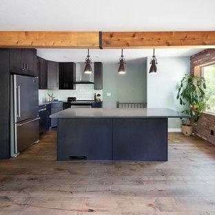Offene, Kleine Industrial Küche in L-Form mit Unterbauwaschbecken, Schrankfronten mit vertiefter Füllung, braunen Schränken, Quarzit-Arbeitsplatte, Küchenrückwand in Weiß, Rückwand aus Keramikfliesen, Küchengeräten aus Edelstahl, braunem Holzboden, Kücheninsel, braunem Boden und grauer Arbeitsplatte in Edmonton
