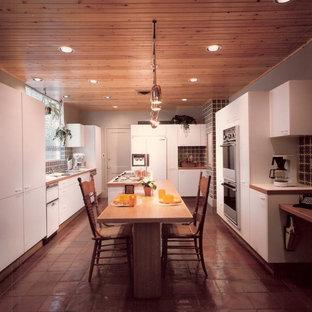 Cette photo montre une cuisine ouverte parallèle moderne avec un évier 3 bacs, un placard à porte plane, des portes de placard jaunes, une crédence multicolore, une crédence en carreau de céramique et un électroménager encastrable.