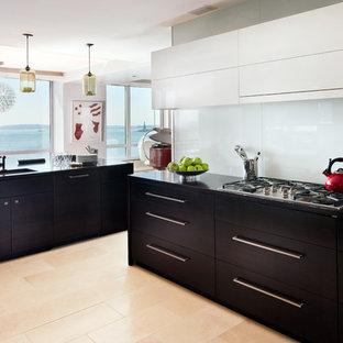 Maritime Wohnküche ohne Insel in U-Form mit flächenbündigen Schrankfronten, Küchenrückwand in Weiß, Glasrückwand, dunklen Holzschränken, Unterbauwaschbecken, Onyx-Arbeitsplatte, Küchengeräten aus Edelstahl und hellem Holzboden in New York