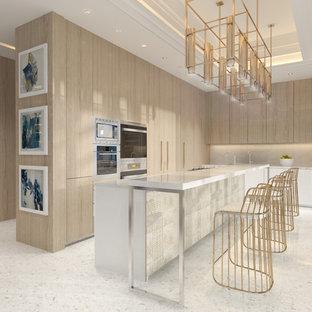 マイアミの広いモダンスタイルのおしゃれなキッチン (フラットパネル扉のキャビネット、ベージュのキャビネット、大理石カウンター、パネルと同色の調理設備、白い床) の写真