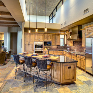 Large l-shaped open plan kitchen in Phoenix with a double-bowl sink, raised-panel cabinets, medium wood cabinets, granite benchtops, stainless steel appliances, slate floors, with island and multi-coloured floor.