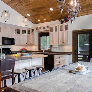 ボストンの中サイズのラスティックスタイルのおしゃれなキッチン (ダブルシンク、シェーカースタイル扉のキャビネット、淡色木目調キャビネット、ラミネートカウンター、黒い調理設備、リノリウムの床) の写真