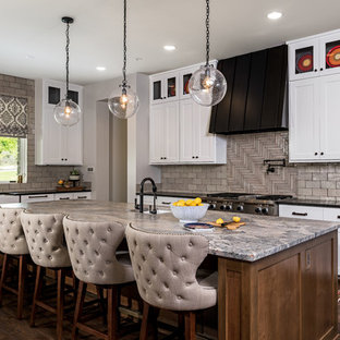 Example of a large country u-shaped brown floor and dark wood floor kitchen design in Other with a farmhouse sink, white cabinets, quartzite countertops, beige backsplash, brick backsplash, stainless steel appliances, an island and shaker cabinets