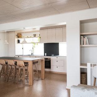 Idéer för maritima linjära svart kök och matrum, med en dubbel diskho, kaklad bänkskiva, svart stänkskydd, stänkskydd i porslinskakel, rostfria vitvaror, korkgolv, en köksö och skåp i ljust trä